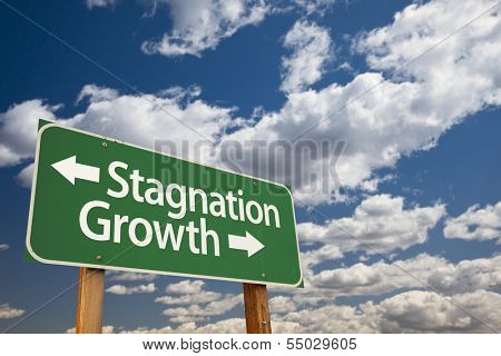 Stagnation or Growth Green Road Sign Over Dramatic Clouds and Sky.