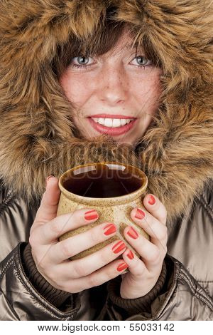 Young smiling girl wearing winter coat heating up with cup of hot tea