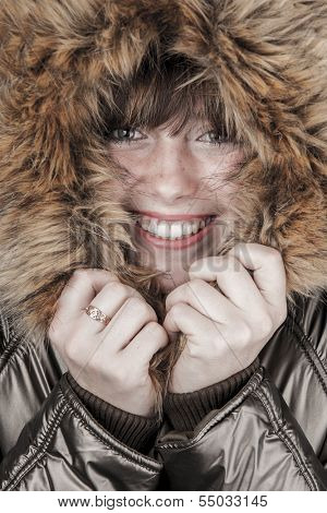 Young smiling girl wearing winter coat warming herself with fur hood up faded vintage colors