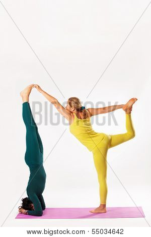senior woman and younger woman practice yoga, headstand and lord of the dance pose, studio shot