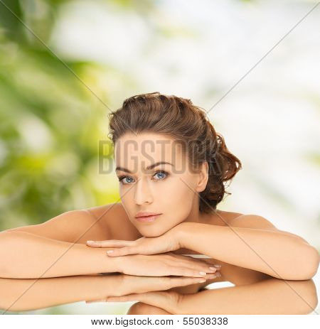 health and beauty concept - dreaming woman with updo and mirror