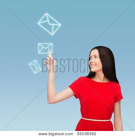 communiction and new technology concept - attractive young woman in red dress pointing her finger at envelope