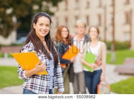 summer holidays, education, campus and teenage concept - smiling female student in with folders and group in the back