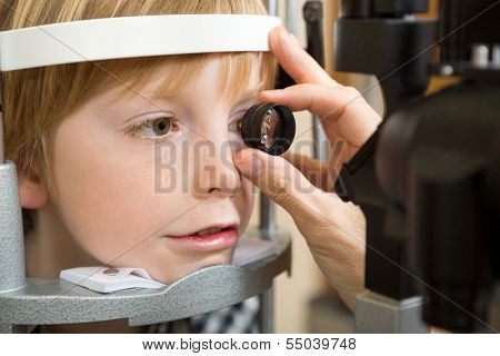 Closeup of male optician's hand examining boy's retina with lens in clinic