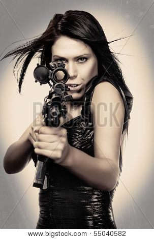 Beautiful young woman poking through scope of army rife