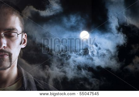 Man dreaming, eyes closed. Moon in cloudy sky background behind his face.