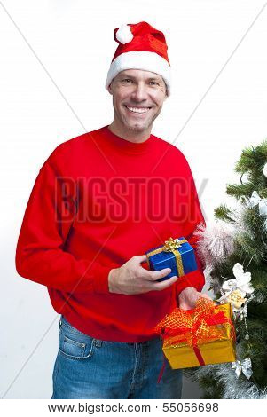 Smiling Christmas Man Wearing A Santa Hat At The Christmas Tree With Gifts