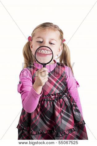 Funny girl showing teeth through a magnifying glass