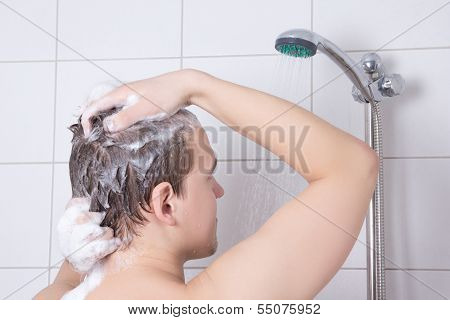 Back View Of Young Attractive Man Washing Hair