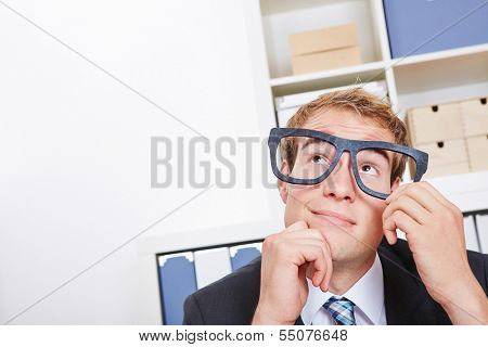Pensive business man in office with nerd glasses looking up
