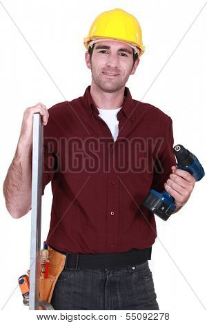 Builder posing with drill and plank