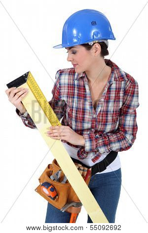 craftswoman measuring a board