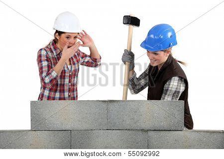 Two women smashing wall
