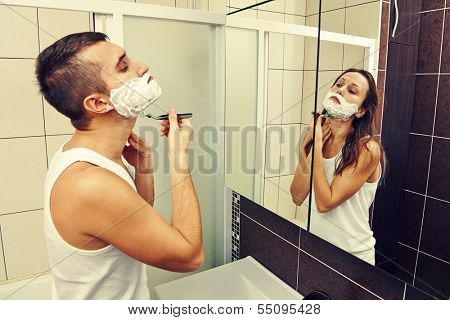 young man shaving and looking at a woman in the mirror