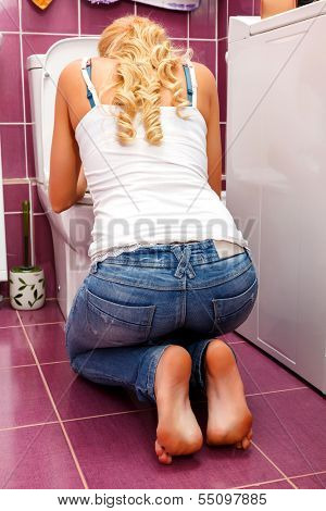 Hangover after a party, woman in the toilet
