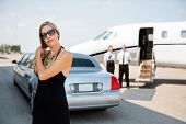 picture of dress-making  - Elegant woman making hair while standing against limousine and private jet - JPG