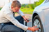 foto of descending  - businessman checks the tire pressure in your car descends - JPG