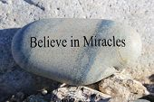 stock photo of miracle  - Positive reinforcement word Believe in Miracles engrained in a rock - JPG