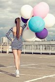 stock photo of latex woman  - Happy young woman with big colorful latex balloons - JPG