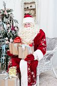 stock photo of saint-nicolas  - Saint Nicolas with gifts sits near the Christmas fir - JPG