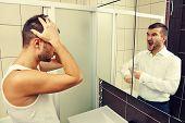 foto of sleepy  - sleepy man looking in the mirror at his angry reflection - JPG