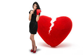 foto of heartbreaking  - Beautiful woman in wearing a boxing glove in front of a broken heart  - JPG