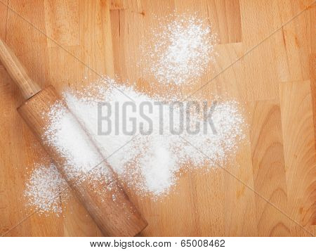 Rolling pin with flour on wooden table. View from above