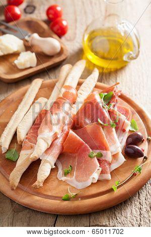 prosciutto ham and grissini bread sticks. italian antipasto