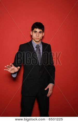 Young Man In Suit Over Red Wall