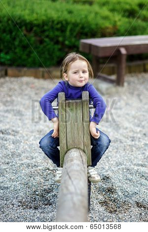 Cute Little Girl Swinging On Seesaw