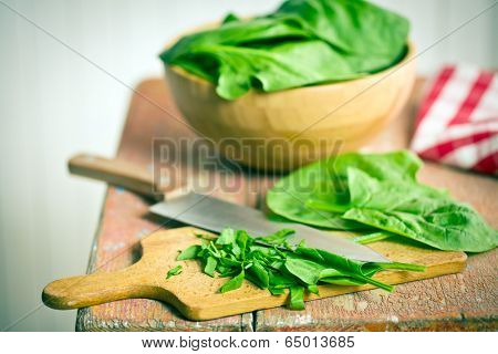 chopped spinach leaves on old wooden table