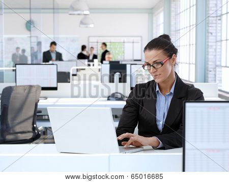 Trustworthy businesswoman working at office desk, using laptop computer.