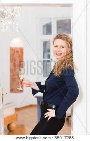 Young business woman at home, drinking sparkling wine in a glass and takes a break at after hour