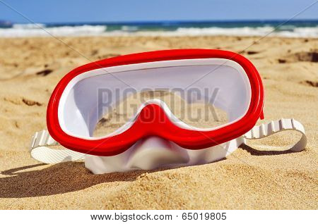 a diving mask in the sand of a beach
