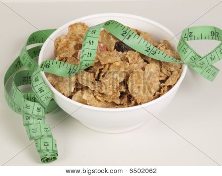 Measurement Tape Wrapped Around Dish With Flakes/concept For Health, Diet