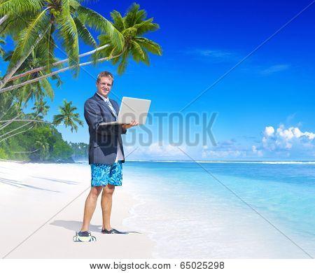 Businessman holding a laptop on a beach.