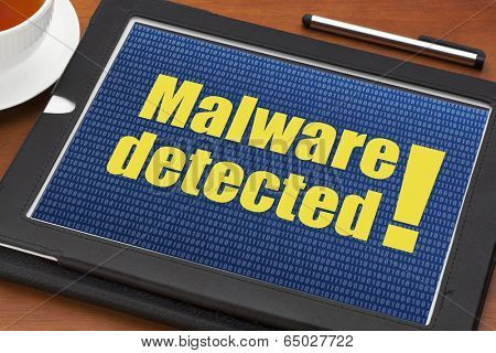 malware detected alert on a digital tablet with a cup of tea