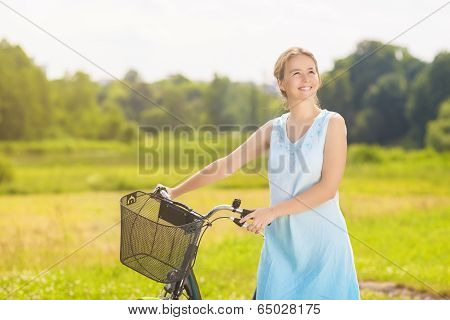 Happy Beautiful Caucasian Blond Having A Stroll In The Park Area With Her Bicycle