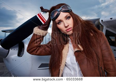 Portrait of young beautiful woman pilot in front of an airplane.