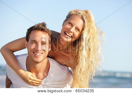 Beach couple fun - lovers on romantic travel doing piggyback in love on honeymoon vacation summer holidays romance. Young happy people, Caucasian woman and man embracing outdoors,