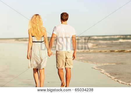 Beach couple holding hands walking at sunset by ocean sea. Beautiful casual young lovers hand in hand walking away with back at rear view. Summer vacation beach travel holidays concept.