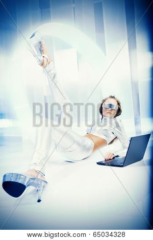 Beautiful young woman in silver latex costume with futuristic hairstyle and make-up working on a laptop. Sci-fi style.
