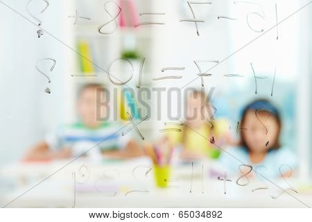 Image of sums written on transparent board with schoolmates on background