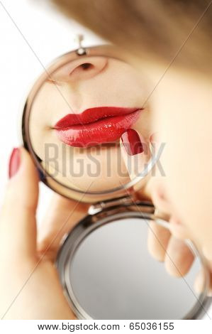 beautiful red lips in a hand mirror