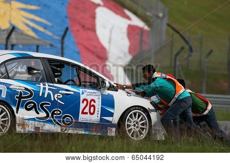 SEPANG, MALAYSIA - MAY 10, 2014: Track marshals push the Honda Civic car of Wijak Lertprasertpakorn off the track after it broke down during the Super 2000 race of the TSS Rd 1 in Sepang Circuit.