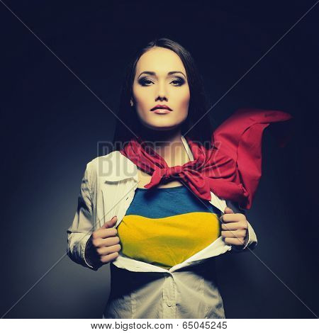 Young woman opening shirt painted in colors of ukrainian flag like superhero. Girl twenty-years-old like young Ukraine fights for independence, democracy and peaceful life. Ukrainian patriot concept.