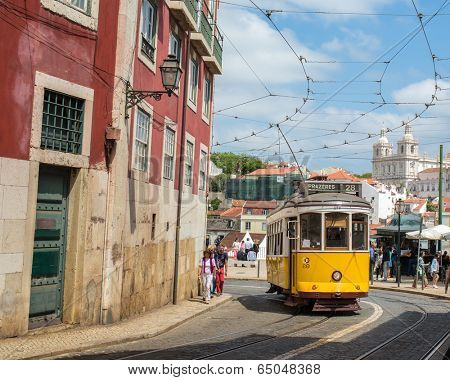 LISBON, PORTUGAL - APRIL 18, 2014: Very touristic place in the old part of Lisbon, with a traditional tram passing by in the city of Lisbon, Portugal.