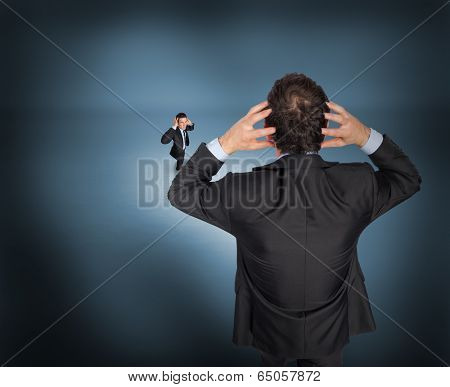 Stressed businessman with hands on head with tiny businessman against purple vignette