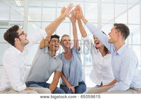 Group therapy in session sitting in a circle high fiving in a bright room