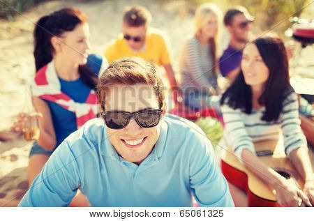 summer, holidays, vacation and happiness concept - smiling man in sunglasses having fun on the beach with company on the back